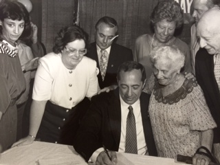 Governor Mario Cuomo with senior advocate Rose Kryzak, Assembylwoman Catherine Nolan and others signing the EPIC program into law, December 1986